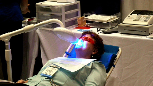 Patient recieving laser teeth whitening treatment, picture courtesy of gruntzooki, Flikr